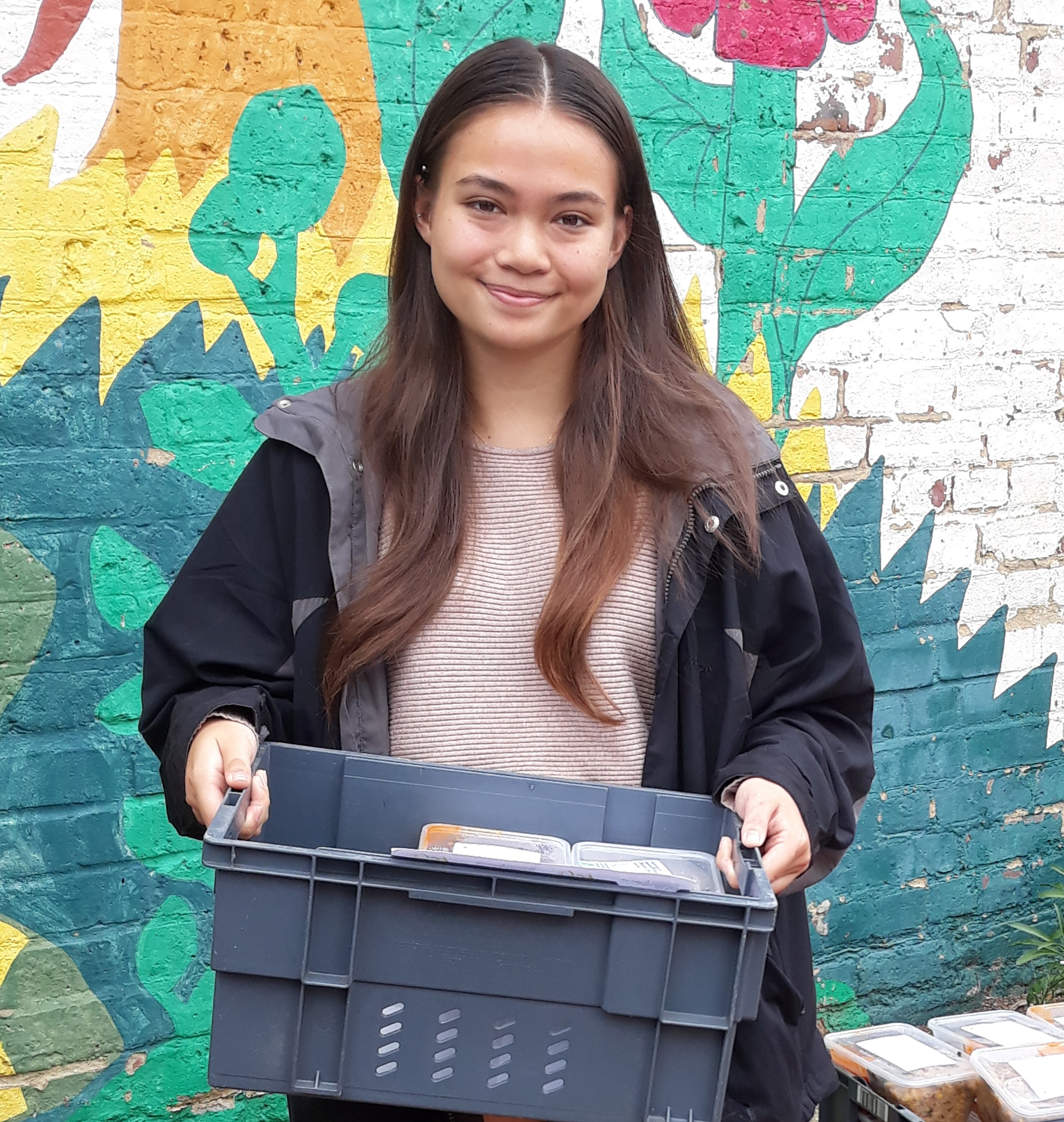 Young volunteer holding a box of food for delivery to local elders