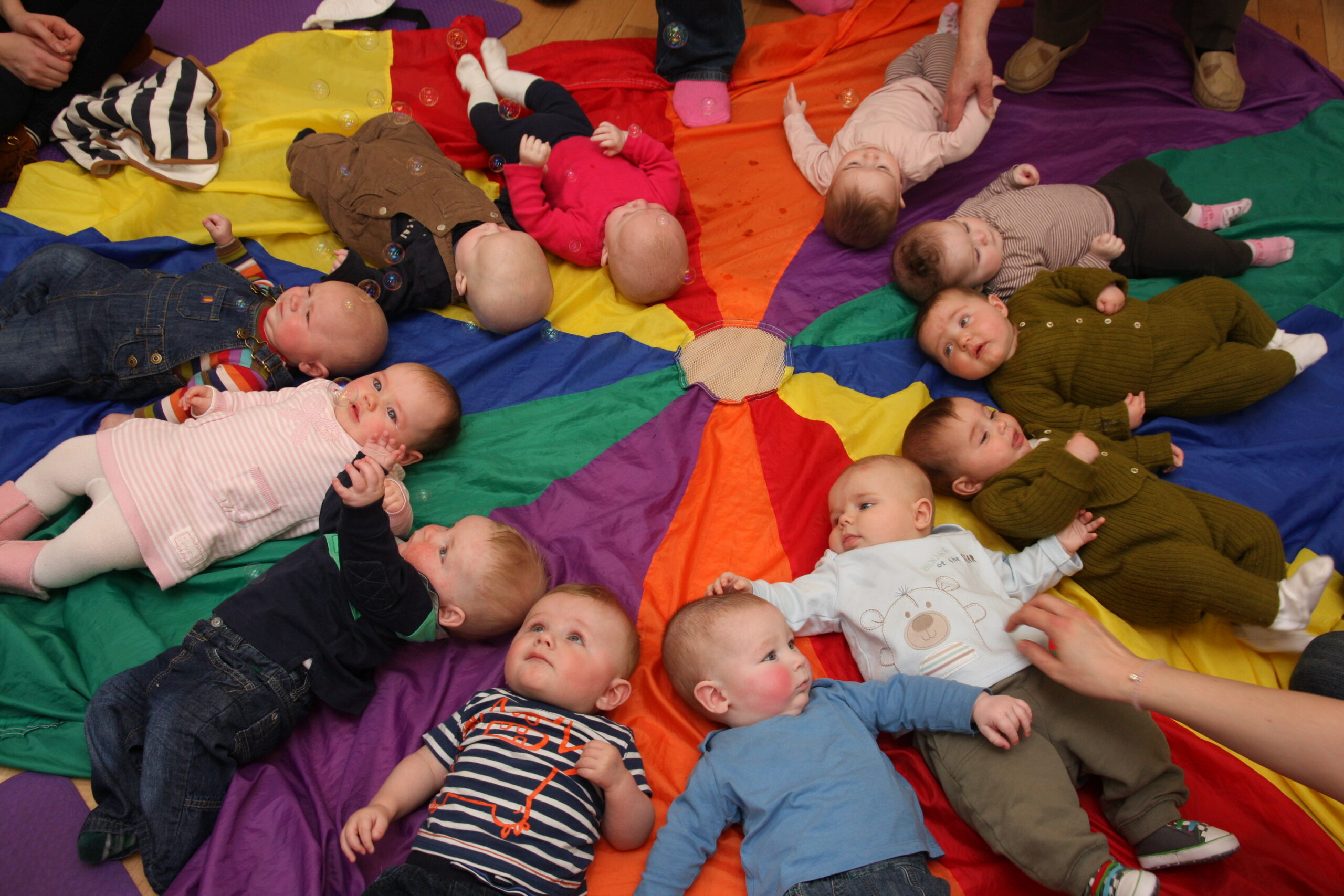 Brightly coloured image of several babies on their backs in a circle